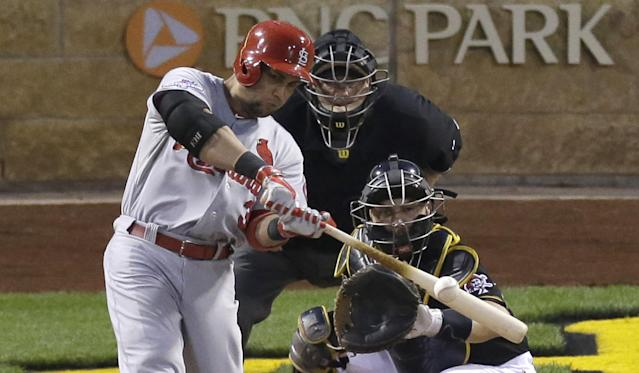 St. Louis Cardinals' Carlos Beltran hits a solo home run in the eighth inning of Game 3 of a National League baseball division series as Pittsburgh Pirates catcher Russell Martin looks on Sunday, Oct. 6, 2013, in Pittsburgh . (AP Photo/Tom Puskar)