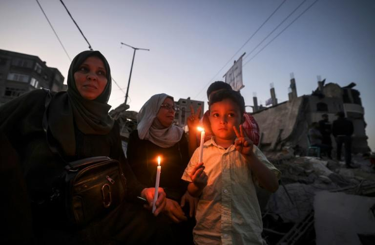 Palestinian children hold candles as they visit the ruins of a building destroyed in recent Israeli air strikes in Beit Lahia in the northern Gaza Strip on May 25