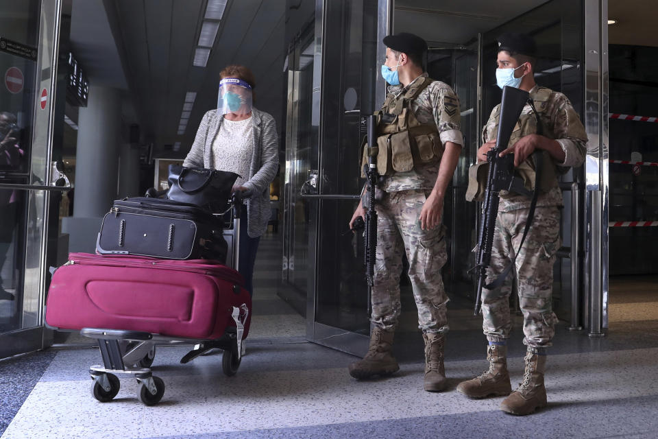 Lebanese soldiers stand guard as a woman leaves the Rafik Hariri International Airport in Beirut, Lebanon, Wednesday, July 1, 2020. Beirut's airport is partially reopening after a three-month shutdown and Lebanon's cash-strapped government is hoping that thousands of Lebanese expatriates will return for the summer, injecting dollars into the country's sinking economy. (AP Photo/Bilal Hussein)