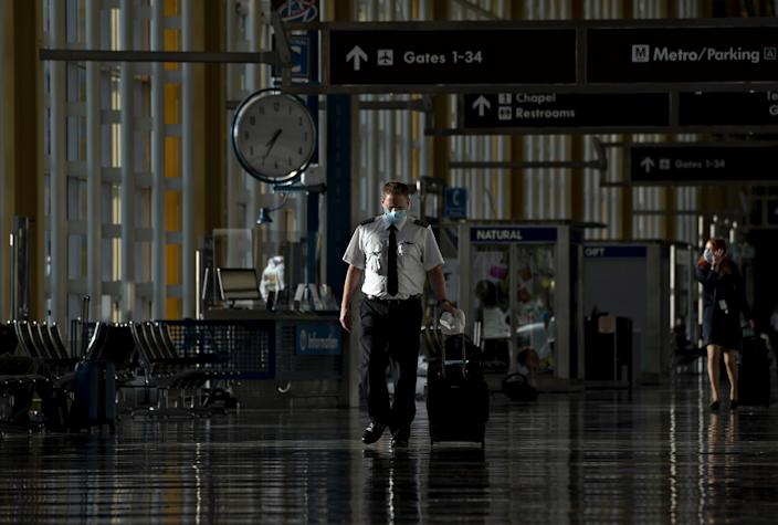A pilot wearing a protective mask walks through Ronald Reagan National Airport in Arlington (Andrew Harrer / Bloomberg via Getty Images)