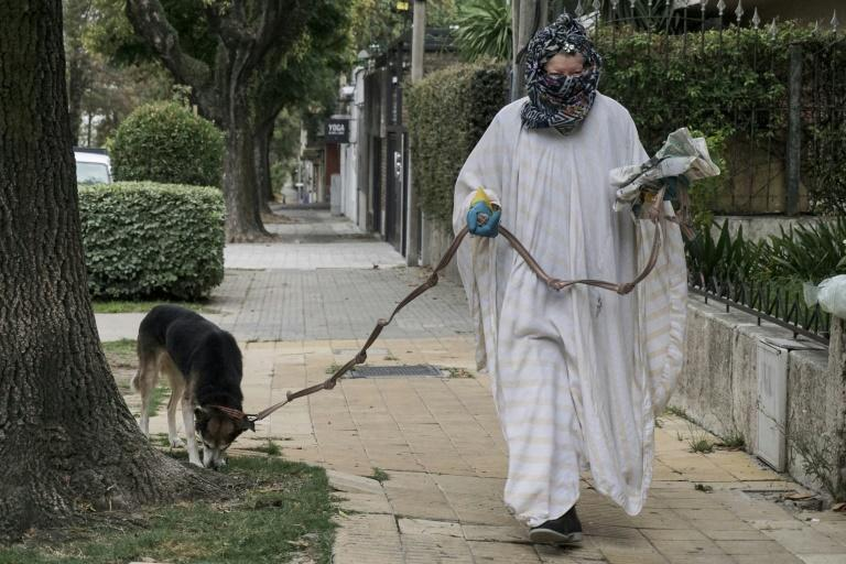 A woman walking her dog in Montevideo uses homemade protective clothing against coronavirus (AFP Photo/EITAN ABRAMOVICH)