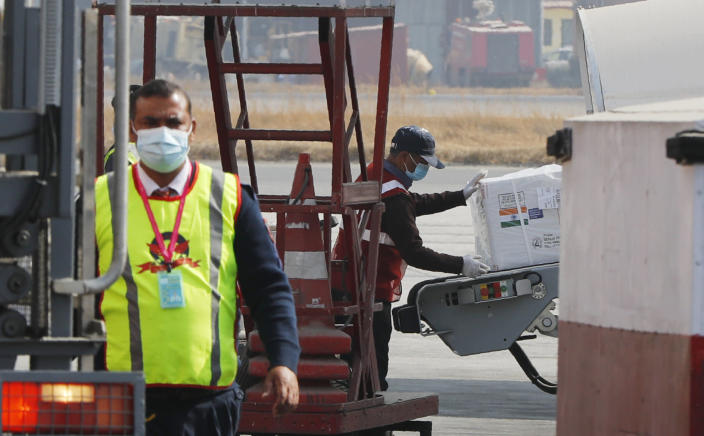 A Nepalese airport ground staff unload a box carrying AstraZeneca/Oxford University vaccine, manufactured under license by Serum Institute of India, arrive at Tribhuwan International Airport in Kathmandu, Nepal, Thursday, Jan. 21, 2021. India sent 1 million doses of a coronavirus vaccine to Nepal on Thursday, a gift that is likely to help repair strained ties between the two neighbors. (AP Photo/Niranjan Shrestha)