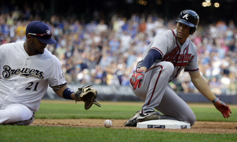 Atlanta Braves' Andrelton Simmons slides safely back to first as Milwaukee Brewers' Juan Francisco (21) can't handle a throw during the ninth inning of a baseball game Saturday, June 22, 2013, in Milwaukee. (AP Photo/Morry Gash)