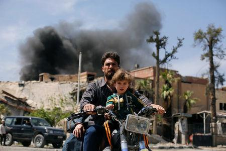A man and a boy ride a motorbike at the city of Douma in Damascus, Syria, April 16, 2018. REUTERS/Omar Sanadiki