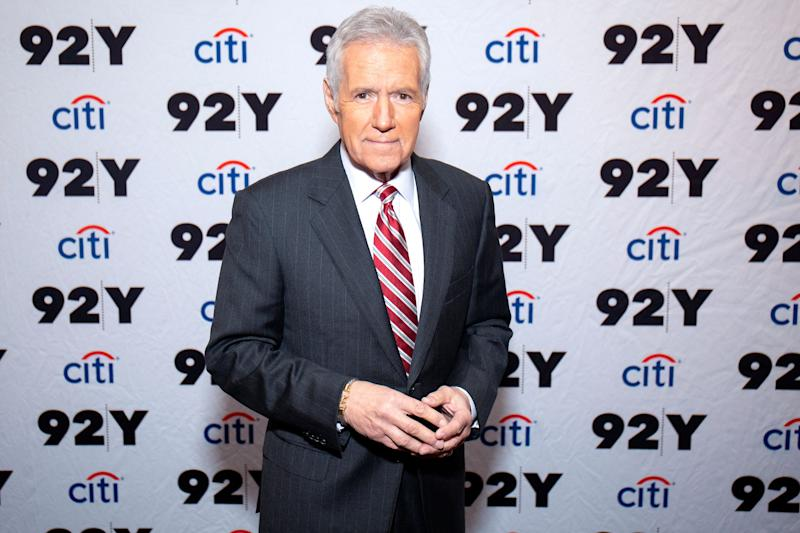 Alex Trebek poses wearing a red and white striped tie