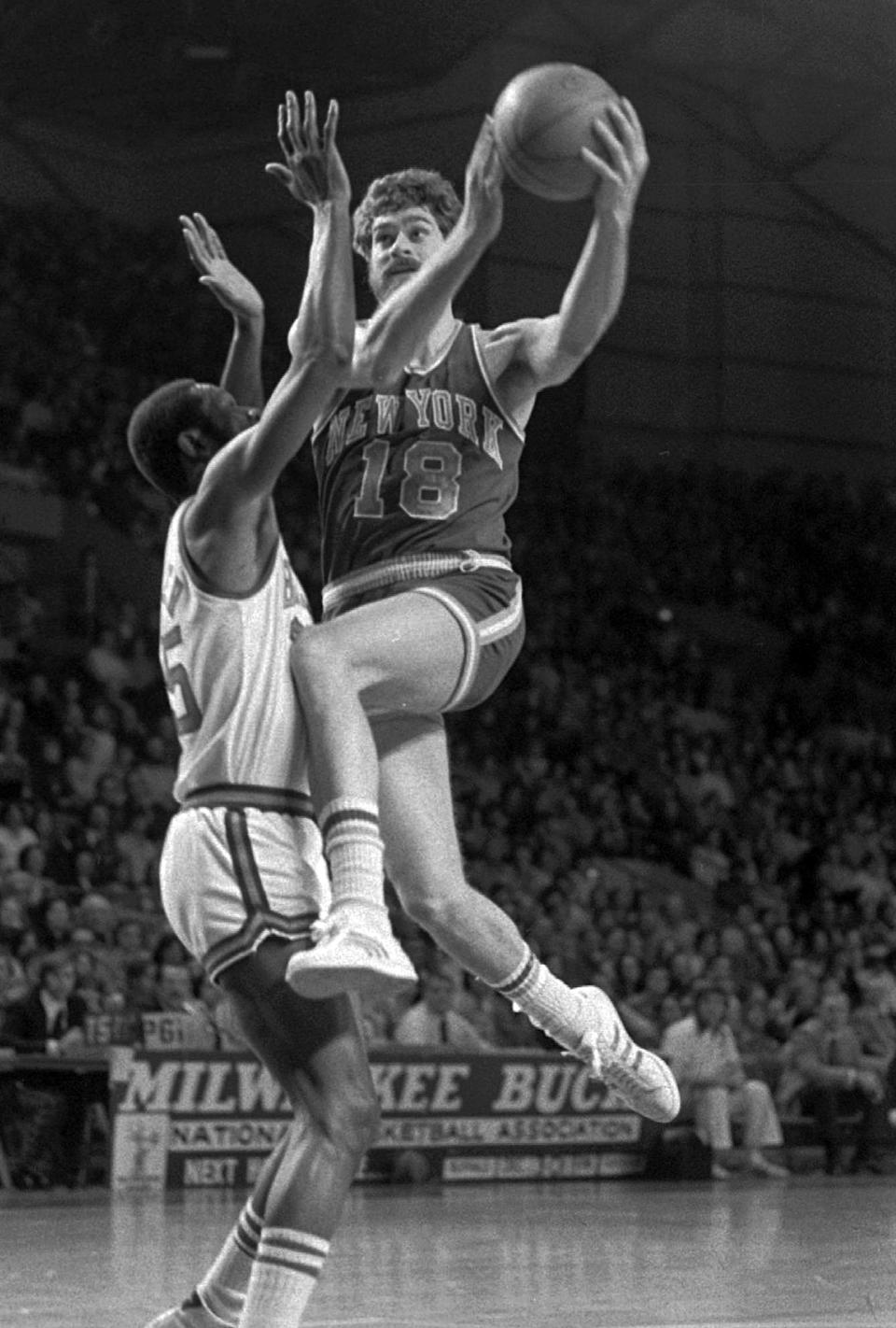 """FILE - In this Dec. 29, 1974 file photo, New York Knicks' Phil Jackson (18) goes to the basket against Milwaukee Bucks' Cornell Warner during an NBA basketball game in Milwaukee. Carmelo Anthony says he has heard that 11-time NBA champion coach Phil Jackson will be """"coming on board"""" in a leadership capacity with the New York Knicks, though cautioned that nothing is yet official. Anthony made the comments Wednesday, March 12, 2014, to reporters in Boston, where the Knicks are playing the Celtics. (AP Photo/File)"""