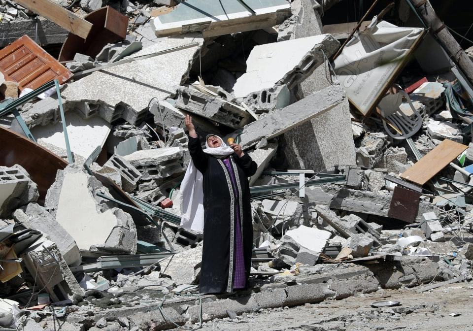A woman cries standing near the rubble of a building.