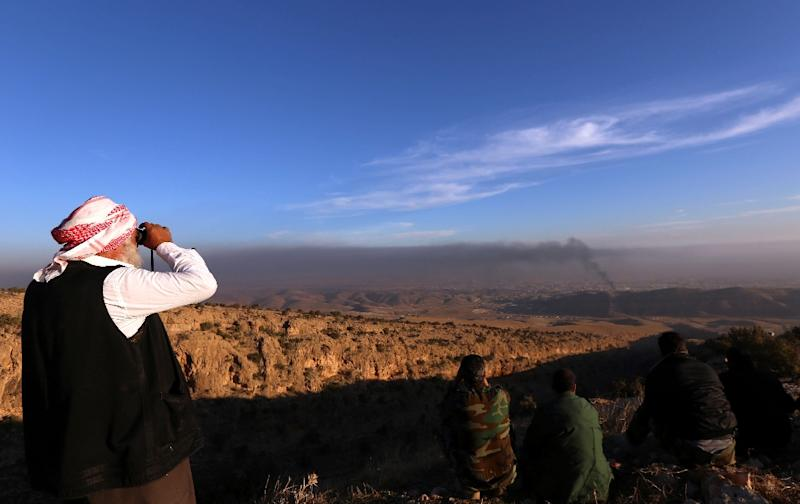 A Yazidi man watches on as Kurdish forces battle to end the Islamic State group's brutal rule over the Iraqi town of Sinjar on November 12, 2015