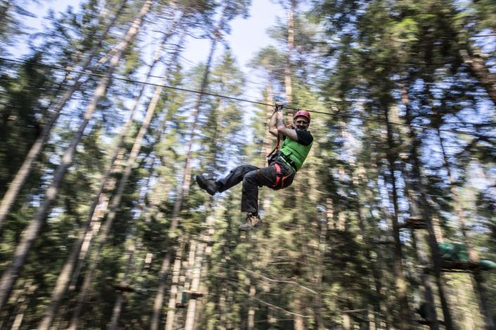 """In this image take on Thursday, April 23, 2020 Diego Fregona, 58, adventure park owner slips on a pulley of the park, in Clusone, near Bergamo, northern Italy. Fregona spent all his savings to repair the damage done to his 10.000sqm park after a whirlwind in October knocked down trees, climbing ropes and suspended trails, only to remain closed with very little money and lots of doubts as to whether he'll ever be able to restart. His words for the Associated Press were """"There isn't a family who didn't have a bereavement, the only thing left to do is to get up again."""" (AP Photo/Luca Bruno)"""