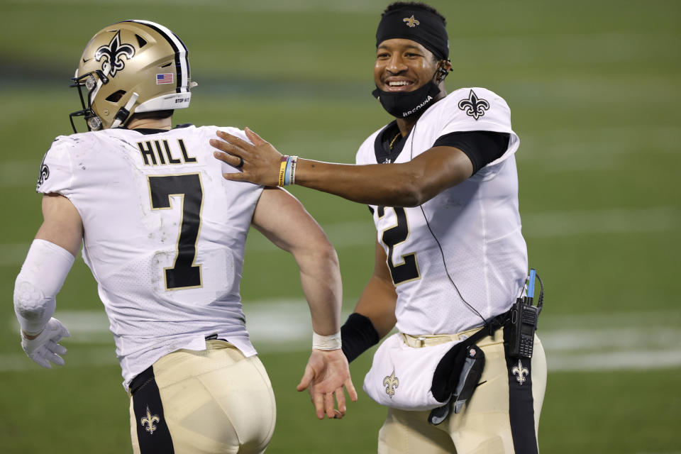Quarterback Jameis Winston #2 of the New Orleans Saints shares a smile as he greets teammate quarterback Taysom Hill #7