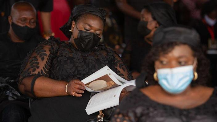 A woman looks through a brochure at the final funeral rites of Ghana's former President Jerry John Rawlings in Accra, Ghana, on January 27, 2021.