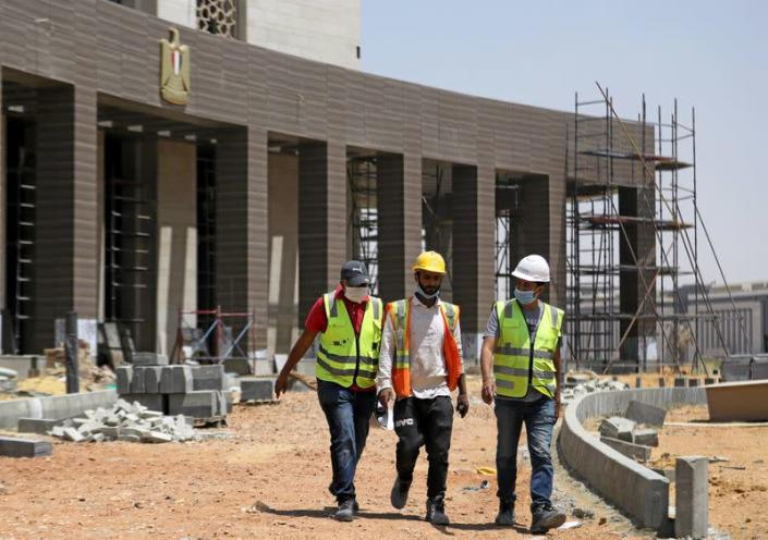 Construction workers walk beside a complex of government buildings under construction in the New Administrative Capital (NAC), east of Cairo
