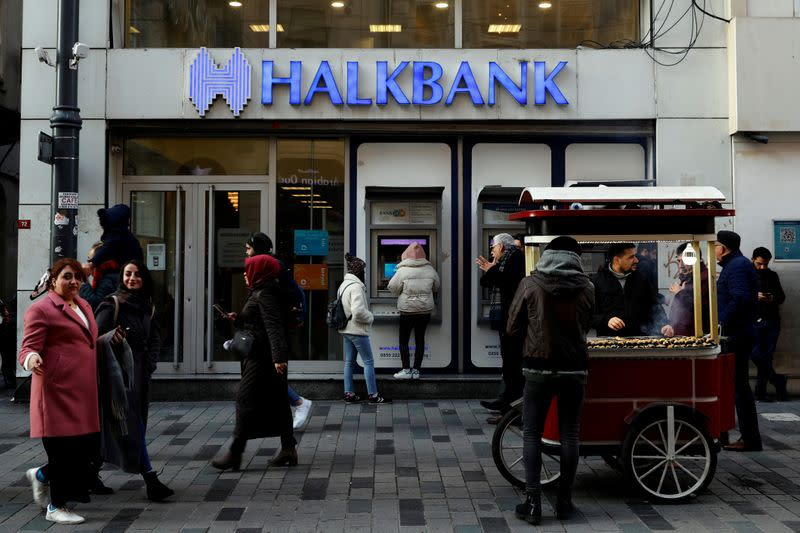 FILE PHOTO: People walk past by a branch of Halkbank in central Istanbul