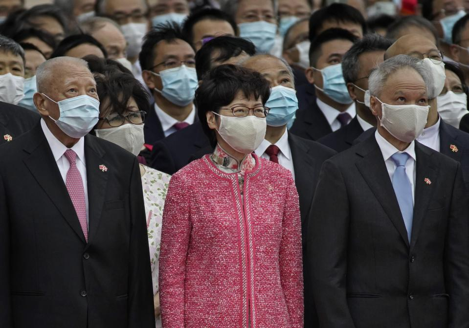 Hong Kong Chief Executive Carrie Lam, center, and former Chief Executive Tung Chee-hwa, left, and Lam's husband Lam Siu-por, right, attend the flag raising ceremony at the Golden Bauhinia Square to mark the 71st anniversary of Chinese National Day in Hong Kong Thursday, Oct. 1, 2020. (AP Photo/Vincent Yu)