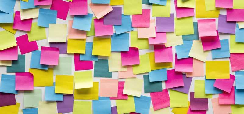 A wall covered in brightly colored post it notes.