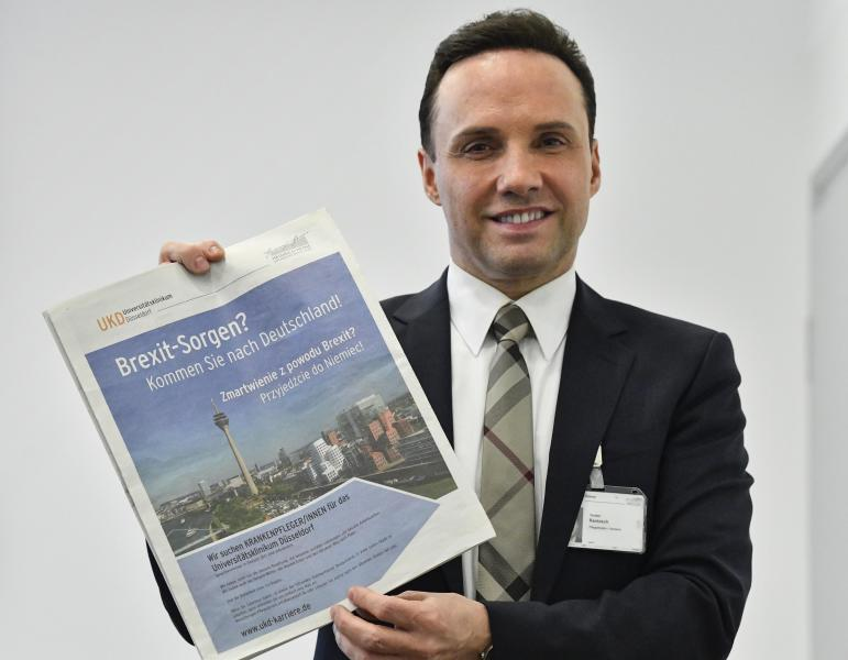 "In this Tuesday, Feb. 12, 2019 photo, the Director of Nursing Torsten Rantzsch poses with his advertisement in Polish newspapers in the UK, reading ""Brexit worries? Come to Germany!"" during an interview with the Associated Press at a meeting room of the University Medical Center in Duesseldorf, Germany. The German hospital wants to hire Polish nurses who may leave the United Kingdom because of the Brexit. (AP Photo/Martin Meissner)"