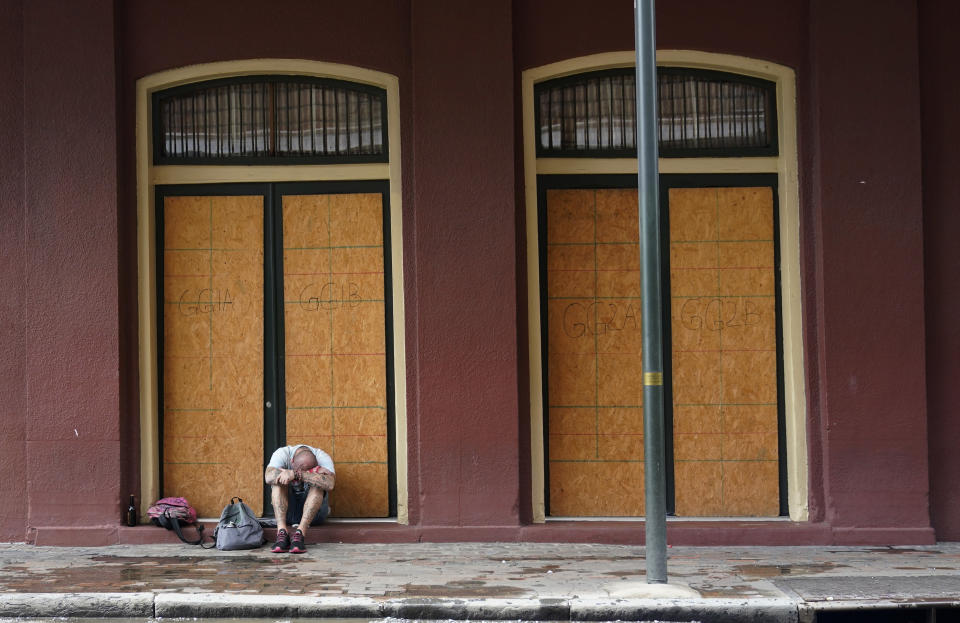 A man sits in front of a French Quarter business with windows boarded in preparation Hurricane Ida, Saturday, Aug. 28, 2021, in New Orleans,. (AP Photo/Eric Gay)