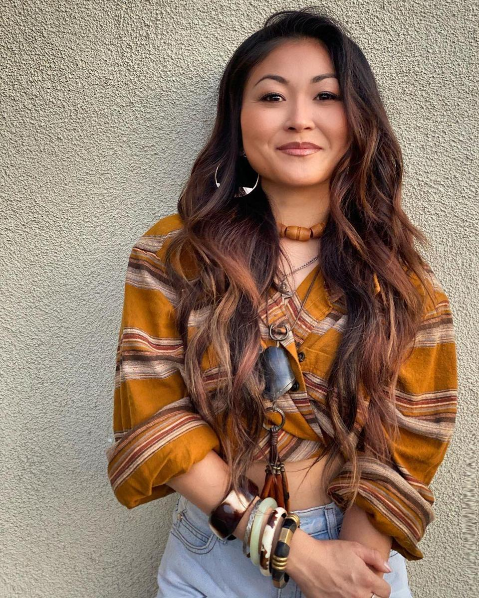 """Extensions aren't just for adding length, they can also be a temporary way to play with color. For this look, Torres started with some brown highlights, and then added in swirls of caramel extensions, one or two shades lighter than her natural hair. """"I love this look because of the color-blocking created,"""" say Torres. """"Warm strands of honey and caramel blended together to create warmth to her naturally dark hair."""""""