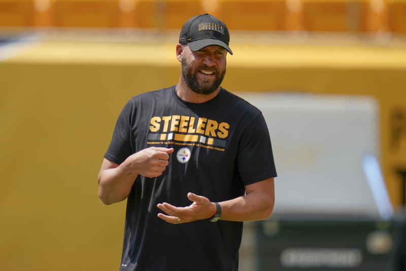 Ben Roethlisberger smiles while on the practice field wearing a black Steelers T-shirt and hat.