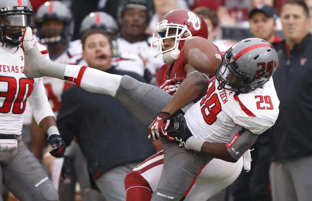 Texas Tech defensive back Olaoluwa Falemi (29) breaks up a pass intended for Oklahoma wide receiver Sterling Shepard (3) in the second quarter of an NCAA college football game in Norman, Okla., Saturday, Oct. 26, 2013. (AP Photo/Sue Ogrocki)
