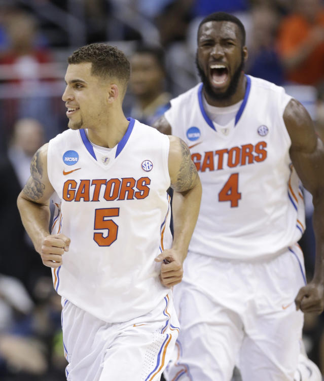 Florida guard Scottie Wilbekin (5) and Florida center Patric Young (4) run off the court after Wilbekin made a 3-point shot against the Pittsburgh at the buzzer to end the first half in a third-round game in the NCAA college basketball tournament in Orlando, Fla., Saturday, March 22, 2014. (AP Photo/John Raoux)