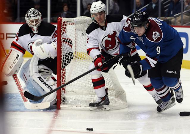 Colorado Avalanche center Matt Duchene, right, pursues the puck with New Jersey Devils defenseman Marek Zidlicky, center, of the Czech Republic, as Devils goalie Cory Schneider covers the net in the second period of an NHL hockey game in Denver, Thursday, Jan. 16, 2014. (AP Photo/David Zalubowski)
