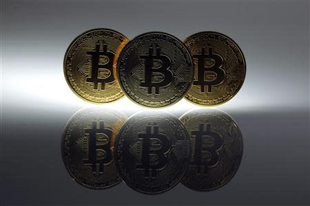 Mock Bitcoins are displayed on a table in an illustration picture taken in Berlin in this January 7, 2014 file photo. Mt. Gox, once the world's biggest bitcoin exchange, looked to have essentially disappeared on February 25, 2014, with its website down, its founder unaccounted for and a Tokyo office empty bar a handful of protesters saying they had lost money investing in the virtual currency. REUTERS/Pawel Kopczynski/File