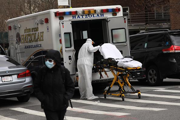 An ambulance driver puts away and cleans a medical gurney outside of Mount Sinai Hospital which has seen an upsurge of coronavirus patients in New York City.