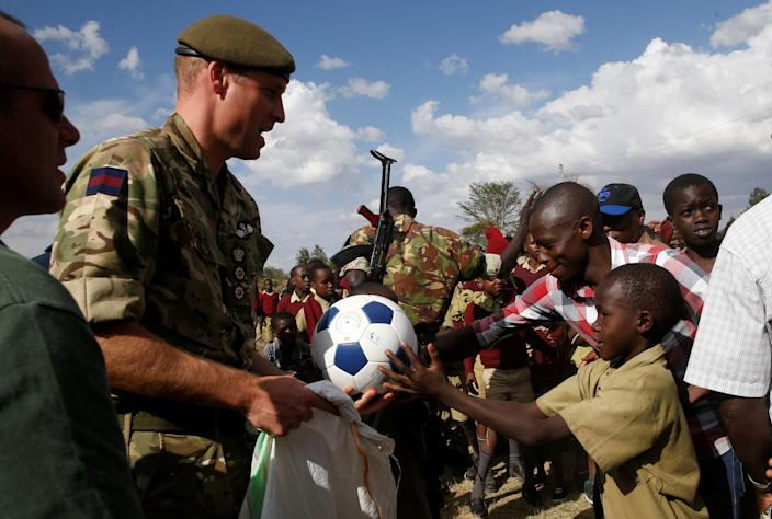 The Duke of Cambridge, Prince William (L) gives sports equipment to pupils during his visit Ol Maiso primary school in Laikipia, Kenya September 30, 2018. REUTERS/Thomas Mukoya