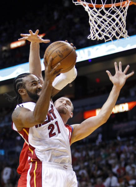 Miami Heat center Ronny Turiaf (21) goes up for a shot against Philadelphia 76ers center Spencer Hawes during the first half of an NBA basketball game, Tuesday, April 3, 2012 in Miami. (AP Photo/Wilfredo Lee)
