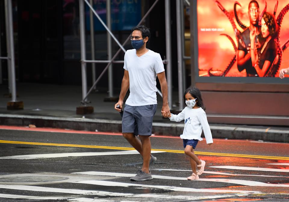 NEW YORK, NEW YORK - AUGUST 16: People wear protective face masks in Hell's Kitchen as the city continues Phase 4 of re-opening following restrictions imposed to slow the spread of coronavirus on August 16, 2020 in New York City. The fourth phase allows outdoor arts and entertainment, sporting events without fans and media production. (Photo by Noam Galai/Getty Images)