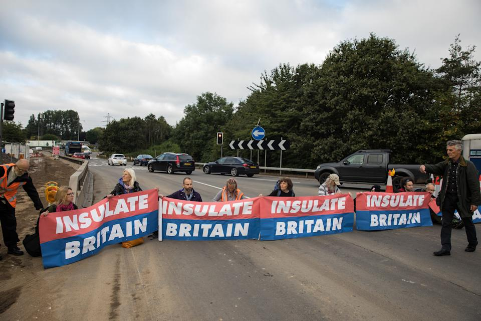 Insulate Britain climate activists block a slip road from the M25 at Junction 25 as part of a campaign intended to push the UK government to make significant legislative change to start lowering emissions on 15th September 2021 in Enfield, United Kingdom. The activists, who wrote to Prime Minister Boris Johnson on 13th August, are demanding that the government immediately promises both to fully fund and ensure the insulation of all social housing in Britain by 2025 and to produce within four months a legally binding national plan to fully fund and ensure the full low-energy and low-carbon whole-house retrofit, with no externalised costs, of all homes in Britain by 2030 as part of a just transition to full decarbonisation of all parts of society and the economy. (photo by Mark Kerrison/In Pictures via Getty Images)