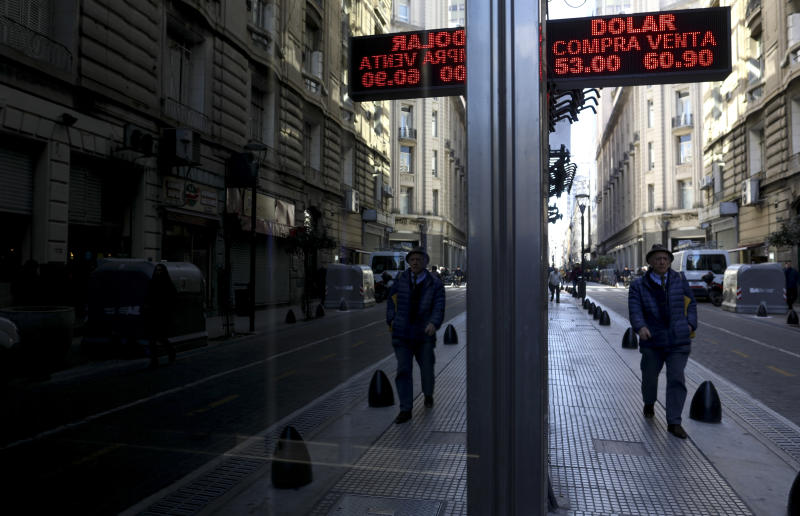 A man walk past a currency exchange board in Buenos Aires, Argentina, Wednesday, Aug. 14, 2019. President Mauricio Macri announced economic relief for poor and working-class Argentines that include an increased minimum wage, reduced payroll taxes, a bonus for informal workers and a freeze in gasoline prices. (AP Photo/Natacha Pisarenko)