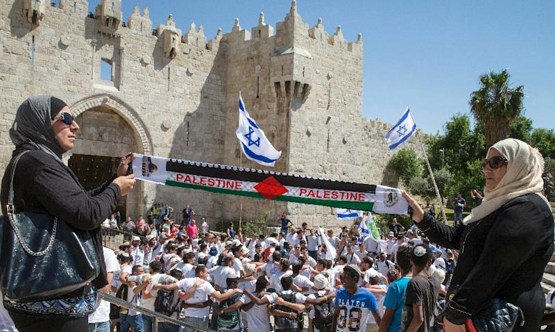 """Palestinian women hold a 'Palestine' scarf as Israeli youths hold their national flag as they take part in the """"flag march"""" through Damascus Gate in Jerusalem's old city during celebrations for Jerusalem Day on May 17, 2015 (AFP Photo/Jack Guez)"""