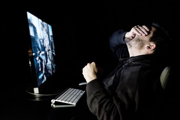 A man slaps his hand over his eyes while playing a video game on his computer.