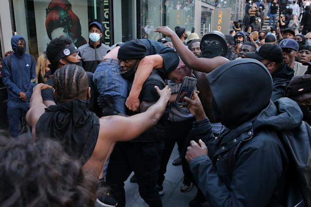 Patrick Hutchinson carries a white man to safety during protests in central London on Saturday. (Getty Images)