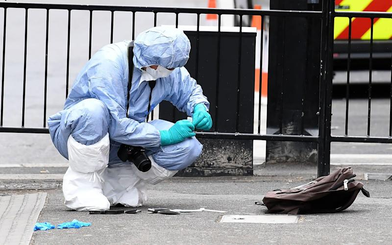 Forensic officer inspects the man's rucksack - Credit: JUSTIN TALLIS/AFP