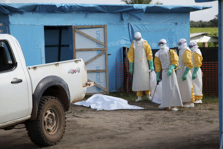 Health workers, wearing head-to-toe protective gear, prepare for work outside an isolation unit in Foya District, Lofa County, Liberia in this July 2014 UNICEF handout photo. REUTERS/Ahmed Jallanzo/UNICEF/Handout via Reuters