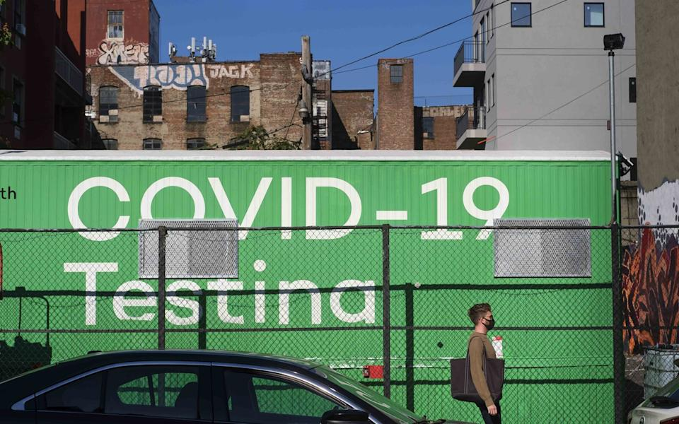 A man walks past a sign for a Covid testing site in the Williamsburg neighborhood of Brooklyn, New York - JUSTIN LANE/EPA-EFE/Shutterstock