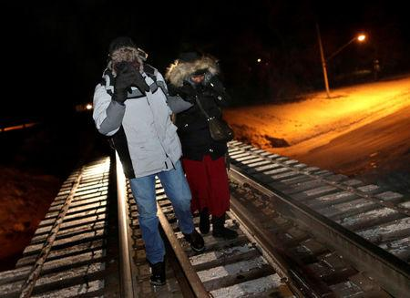 FILE PHOTO - Refugees walk along railway tracks from the United States to enter Canada at Emerson, Manitoba, Canada, on February 26, 2017. REUTERS/Lyle Stafford/File Photo