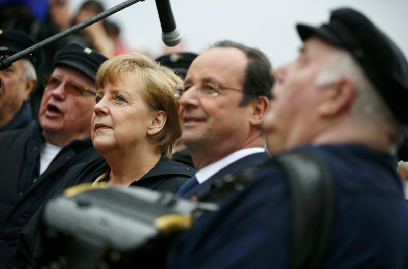 German Chancellor Angela Merkel, 2nd left, and French President Francois Hollande, 2nd right, listen to a Shanty choir before embarking on the ship Nordwind in Sassnitz on Ruegen island in the Baltic sea, Germany, Friday, May 9, 2014. (AP Photo/Thomas Peter, Pool)