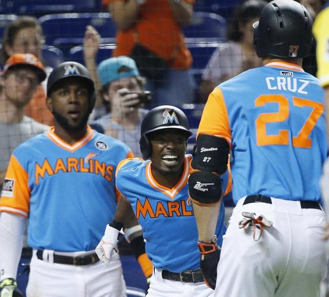 Giancarlo Stanton is congratulated by Dee Gordon (center) and Marcell Ozuna (left) after connecting for his 48th home run of the season. (AP)