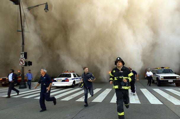 PHOTO: Policemen and firemen run away from the huge dust cloud caused as the World Trade Center's Tower One collapses after terrorists crashed two hijacked planes into the twin towers, Sept. 11, 2001 in New York City. (Jose Jimenez/Primera Hora/Getty Images, FILE)