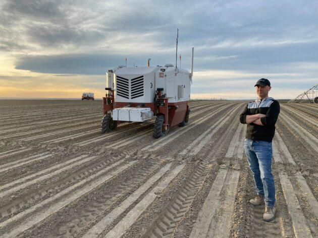 Carbon Robotics CEO Paul Mikesell in a farm field with his company's autonomous weeder. The robot uses laser light to zap as many as 100,000 weeds an hour. (Carbon Robotics Photo)