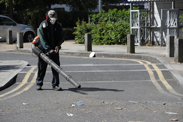 Volunteers clean up in Overton Road on the Angell Town estate in Brixton, south London, where riots and violent confrontations with police took place overnight. (PA)
