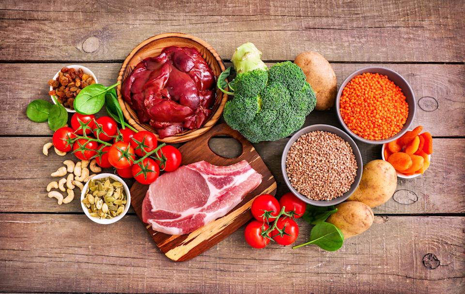 Iron sources on wooden background: liver, beef, raisins, keshew, spinach, tomatoes, potatoes, buckwheat, pumpkin seeds, lentil, broccoli, dried appricots. Top view.