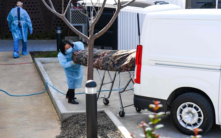 Medical staff remove a body from a care home in Melbourne - GETTY IMAGES