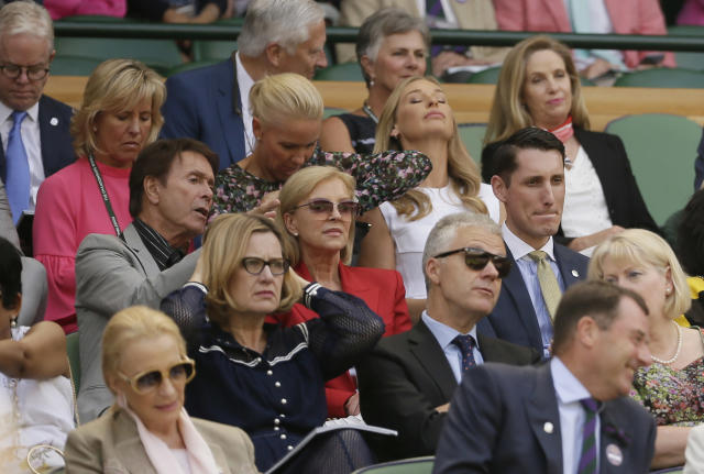 Britain's Cliff Richard, left, sits in the Royal Box on Centre Court ahead of the women's singles semifinal match between Angelique Kerber of Germany and Jelena Ostapenko of Latvia at the Wimbledon Tennis Championships, in London, Thursday July 12, 2018. (AP Photo/Tim Ireland)