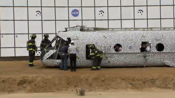 Researchers and firefighters do a preliminary check on the damage moments after the crash test.