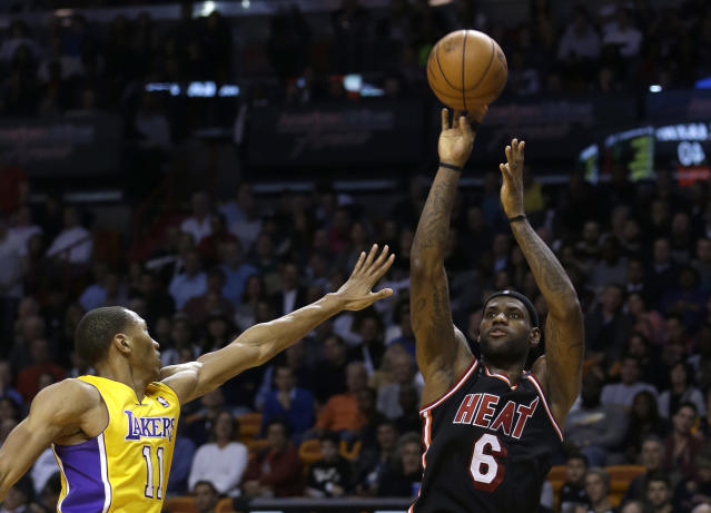 Miami Heat forward LeBron James (6) shoots for three points over Los Angeles Lakers forward Wesley Johnson (11) during the second quarter of an NBA basketball game in Miami, Thursday, Jan. 23, 2014. The Heat won 109-102. (AP Photo/Alan Diaz)